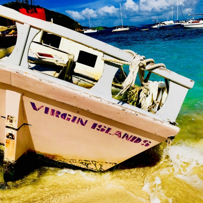 "A boat on a beach with the text ""Virgin Island"" on it."