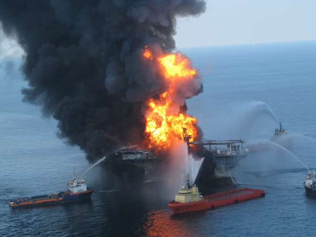 Vessel attempting to put out a fire on a larger rig.
