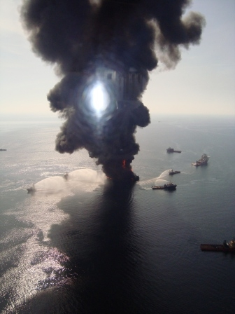 Smoke plumes rising from a structure in the water surrounded by vessels.