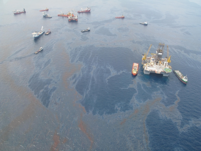 An aerial view of oil on water with various vessels.