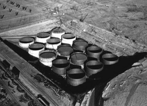 A black and white photo of large containers in the ground.