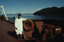 "A man standing on a ship next to a life ring that reads ""Exxon Valdez."""