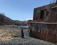 A man on a beach looking at an abandoned barge.
