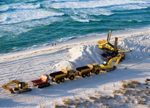 Several trucks and other heavy machinery lined up on a sanding beach with ocean waves in the background.