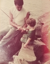 A father and his son fishing at a lake.