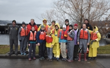 A group of people in life jackets pose for a photo.