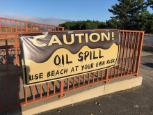 "A sign reading ""Caution: Oil Spill."""