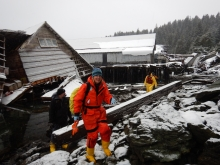 A woman in response gear with a collapsed structure covered in snow behind her.
