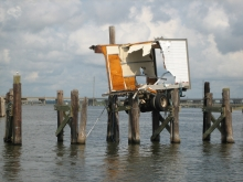 A part of a semi-truck trailer on the remains of a damaged dock above the water.