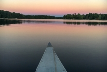 A sunset on a lake as seen from a kayak or a paddleboard.