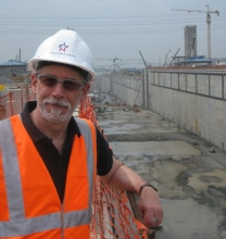 A man in a hard hat and orange vest with an empty canal behind him.