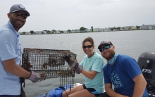 Three people holding up a crabbing cage.