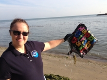 A woman on a beach holding up a birthday balloon.