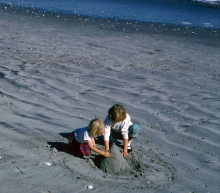 Two kids making a sand castle on a beach.