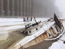 A sunken vessel in an icy-covered body of water with responders in the background.