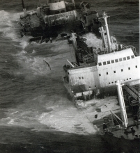 An old black and white photo of a grounded vessel.