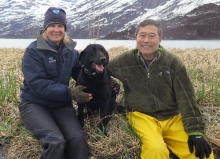 A man, a woman, and a dog with a mountain in the background.