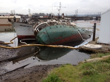 An overturned vessel next to another vessel with pollution boom around it.
