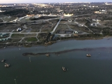 An aerial view of dark crude oil in a body of water along an urban shoreline.