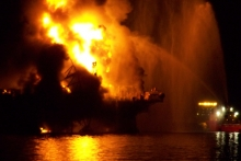 A dark and blurry image of an oil rig on fire.