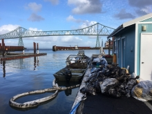 A boat next to a dock with garbage bags filled with oiled debris on it. A bridge is in the background