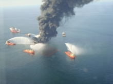 Smoke rising from a structure in the water surrounded by other vessels.