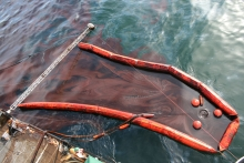 A skimmer surrounding an oil sheen in the water.