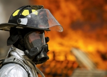 A firefighter in full gear with a fire blazing in the background.