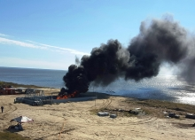 A fire with black smoke rising up from it enclosed in a structure on a sandy beach with water in the background.