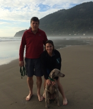A man, a woman, and a dog posing on a beach for a photo.