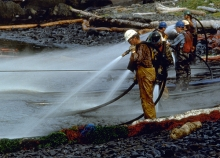 Workers spraying a rocky shoreline with high-pressure water.