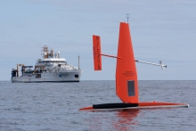 A saildrone in the water with a vessel in the background.