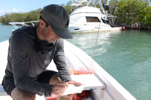 A man sitting on a boat writing on a clipboard.