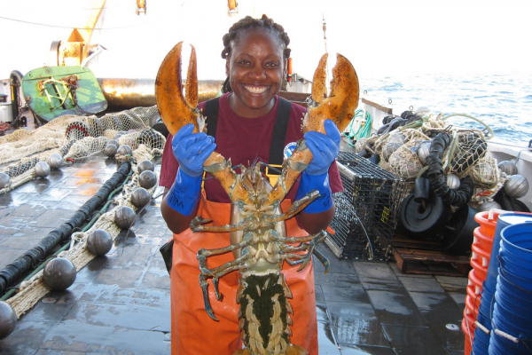 A person holding up a lobster.