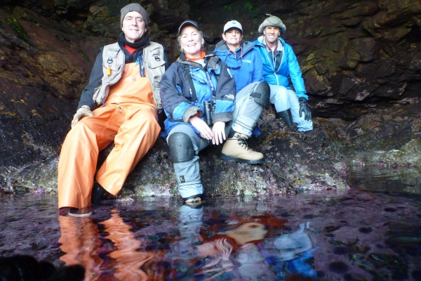Four people pose together in a cave with water.