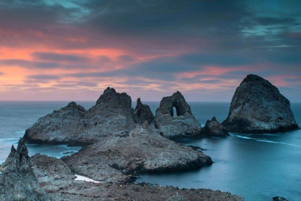 "Rocky outcrops known as the ""Devil's Teeth"" in the water at sunset."