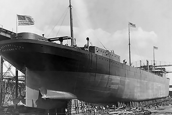 A black and white image of a vessel on land under construction.